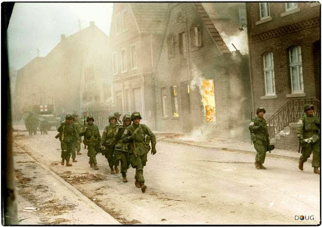 Troops of the 17th U.S. Airborne Division, First Allied Airborne Army, march past a blazing building in Appelhülsen, Germany, as they advance toward the city of Münster, nine miles to the northeast. First Allied Airborne Army troops had landed east of the Rhine river on March 24th 1945. (Colorized by Doug)