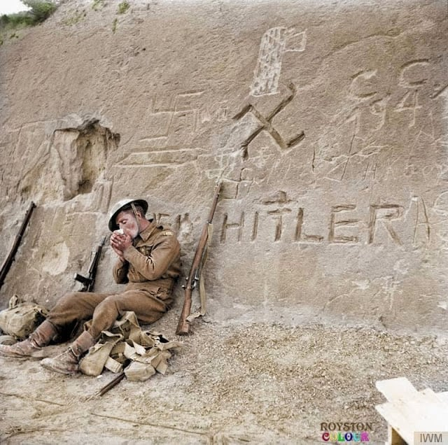 An Allied Soldier takes a break during the approach to Tripoli, Libya beside a swastika and the words 'Heil Hitler' that have been carved into a rocky hillside during January 1943. (Source - © IWM E 21788. Colorized by Royston Leonard from the UK)