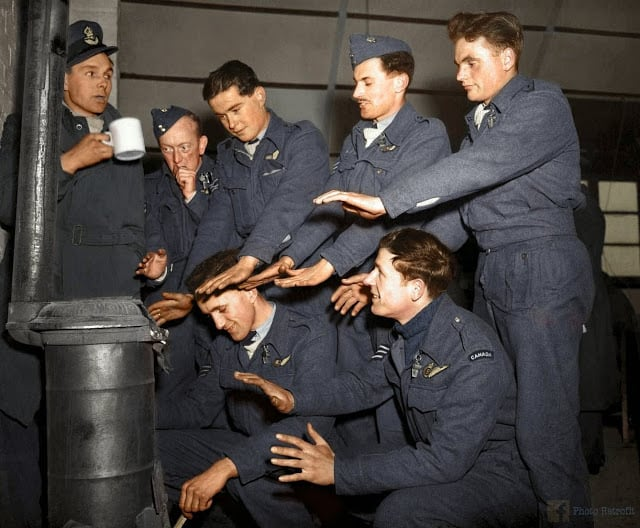 "The crew of Avro Lancaster ""C for Charlie"" of No. 44 (Rhodesia) Squadron RAF, try to warm themselves in their Nissen hut quarters at Dunholme Lodge, Lincolnshire, England, after returning from a raid on Stuttgart, 2nd of March 1944. (Source - © IWM (CH 12379. Colorized by Paul Edwards)"