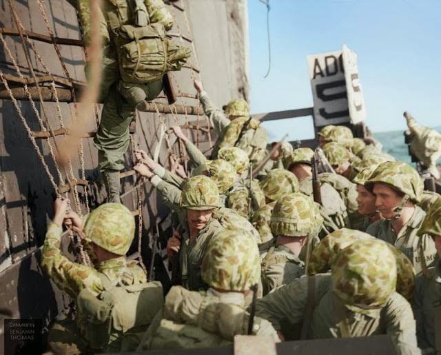 United States Marines climbing down the nets into landing craft during the Battle of Peleliu, September-November 1944. (Photographer: Griffin Image courtesy of the United States Marine Corps History Division, Peleliu 117058. Colorized and researched by Benjamin Thomas from Australia)