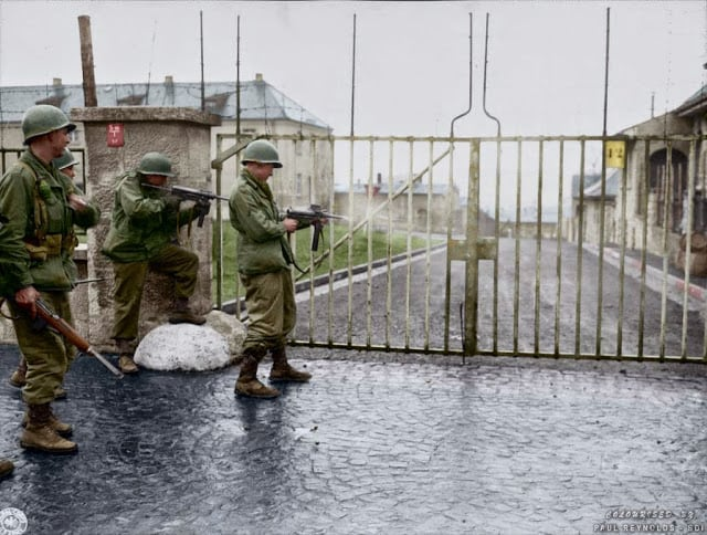 "US troops from Combat Command B of the U.S. 14th Armored Division entering the Hammelburg Prison in Germany by opening the main gate with bursts of their M3 ""Grease Guns"". Hammelburg, Germany. April 6, 1945. (Colorized by Paul Reynolds. Historic Military Photo Colourisations)"
