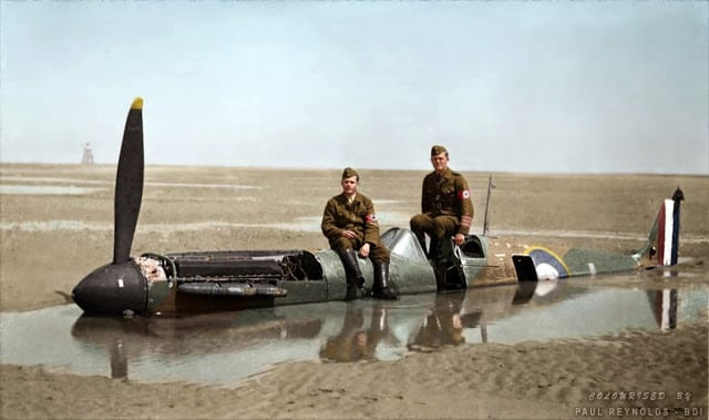 Two German members of the Organisation Todt (involved in the construction of the Atlantic Wall) are sitting on the Spitfire brought down on the wet sands at Calais by Flying Officer Peter Cazenove. It had been hit by a single bullet from a German Dornier bomber. The plane was consumed by the sandy beach and remained there for 40 years. (Colorized by Paul Reynolds. Historic Military Photo Colourisations)