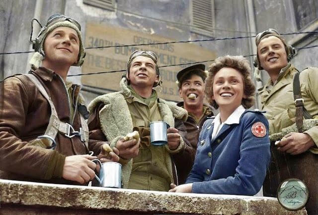From Left to Right, B-25 crew members: Sgt. John C. Bellendir (Gnr.), Chicago; Sgt. Raymond J. Swingholm (Eng/Gnr.), Lebanon, PA; Sgt. Harris B. Pate (Rd/Gnr.), Hamlet, NC; Red Cross Clubmobile Worker, Peggy Steers from White Plains, NY. and T/Sgt. Aubrey Chatters (Rd/Gnr.), Milington MI. All from the 321st Bombardment Group, 447th Bombardment Squadron,12th Air Force. Alesani Airfield, Corsica, 2nd of July 1944. (Photographer - Ollie Atkins, reporter for the American Red Cross. Colorized by Lori Lang from America)