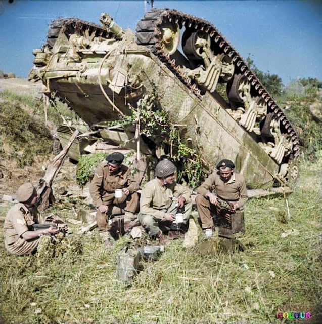 The crew of an up-ended (M4A1) Sherman tank of the 7th Armoured Brigade enjoy a 'brew' beside their vehicle while waiting for a recovery team, on the 'Gothic Line' in Italy, 13th of September 1944. Their tank overturned after slipping off a narrow road in the dark. (Source - IWM NA 18551 - Dawson (Sgt), No 2 Army Film & Photographic Unit. Colourised by Royston Leonard UK)